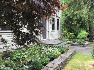 stone wall and patio with plantings trout lily garden design bedford ny